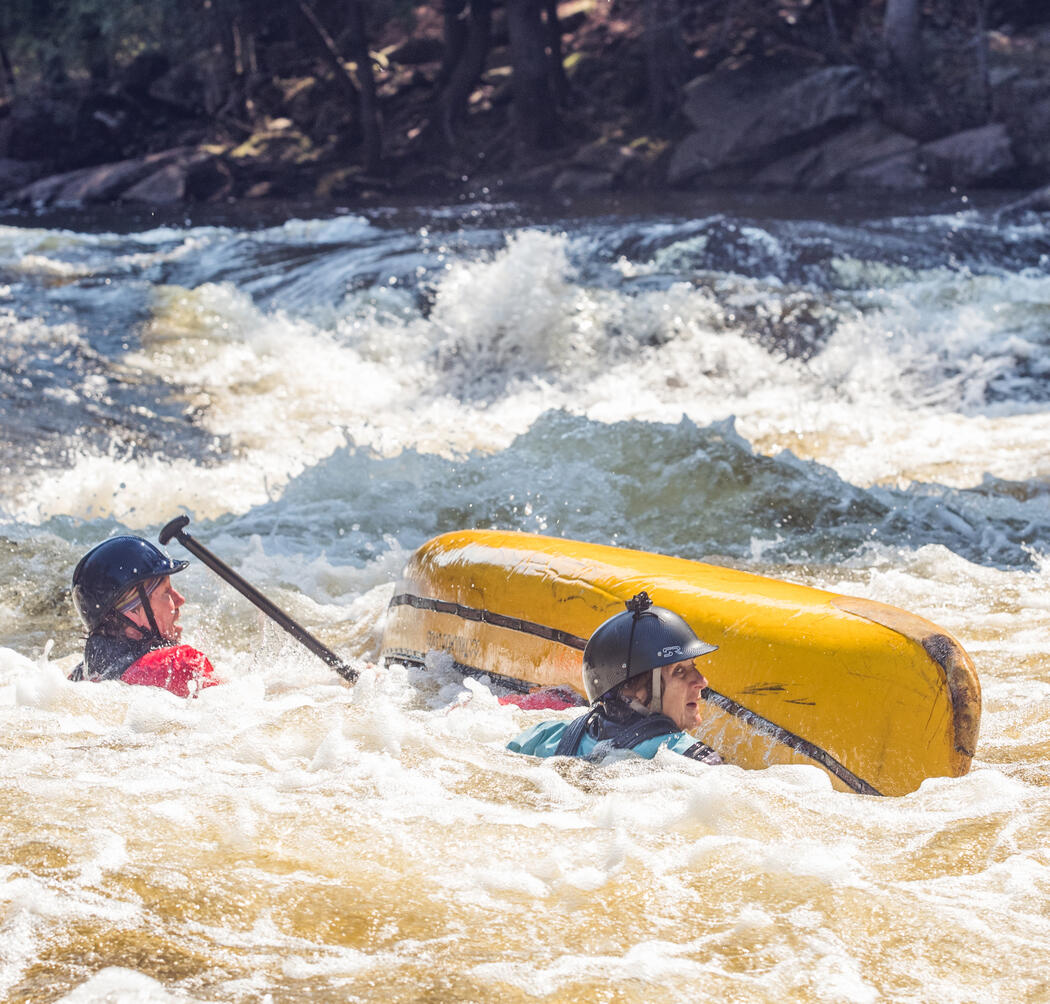 Two paddlers in whitewater beside overturned yellow canoe