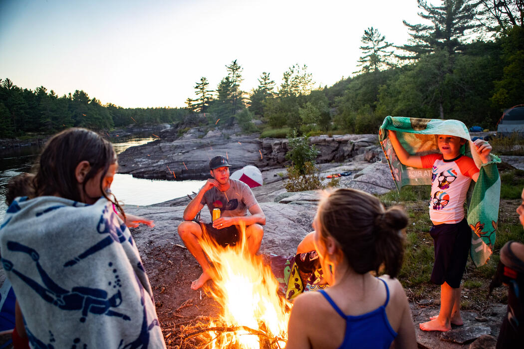 Kids and adults gathered around a campfire by a river.