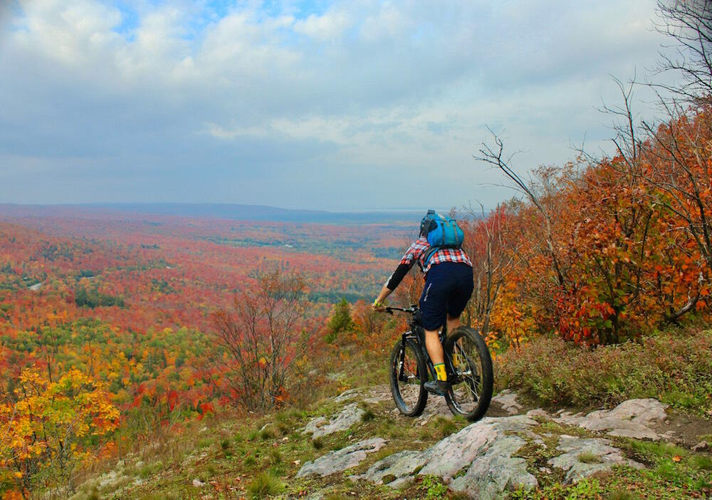 Cyclist riding a rocky path in fall on high hill