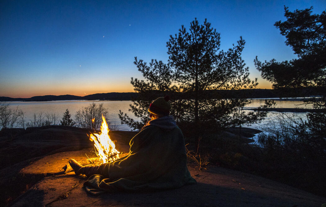 Person sitting at campfire at sunset.