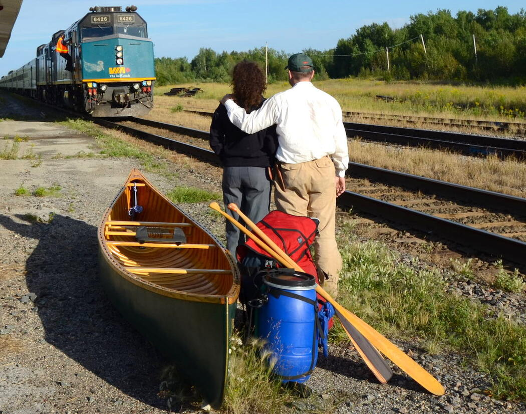 Man and woman standing beside canoe and gear while train approaches.