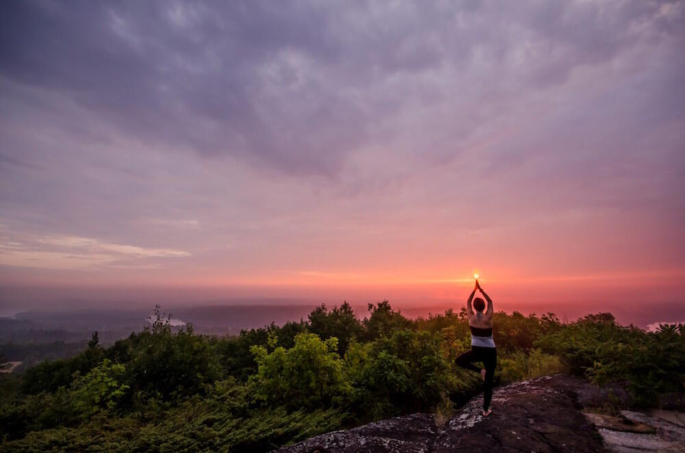 Woman doing yoga on top of a cliff at sunset.