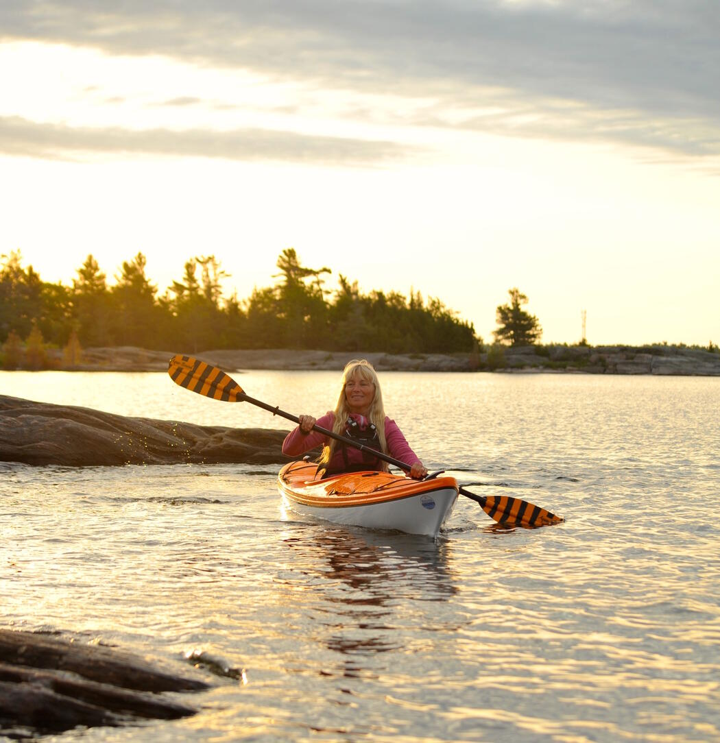 Woman paddling a yellow and white kayak a sunset.