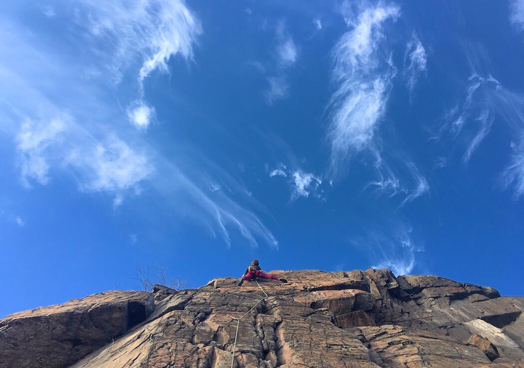 Person climbing half way up tall rock face with blue sky and wispy clouds.