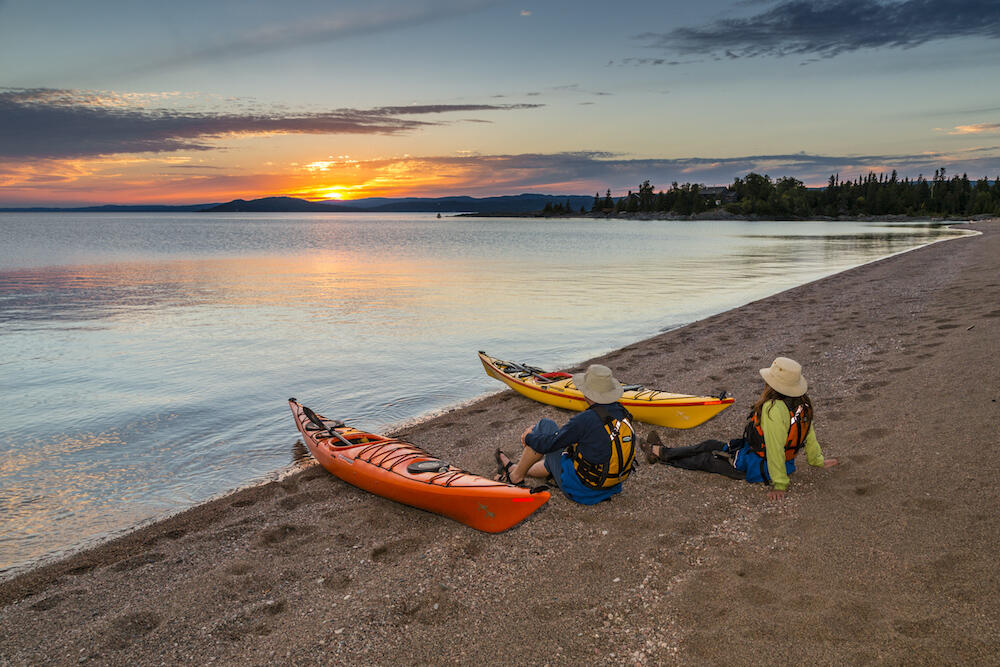 A couple sitting on sandy beach beside kayaks with sun setting over water