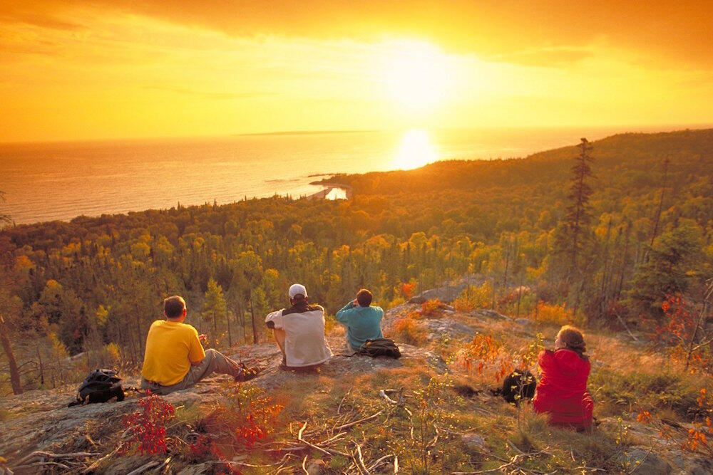 Group of hikers sitting on a high rock lookout overlooking Lake Superior at sunset.
