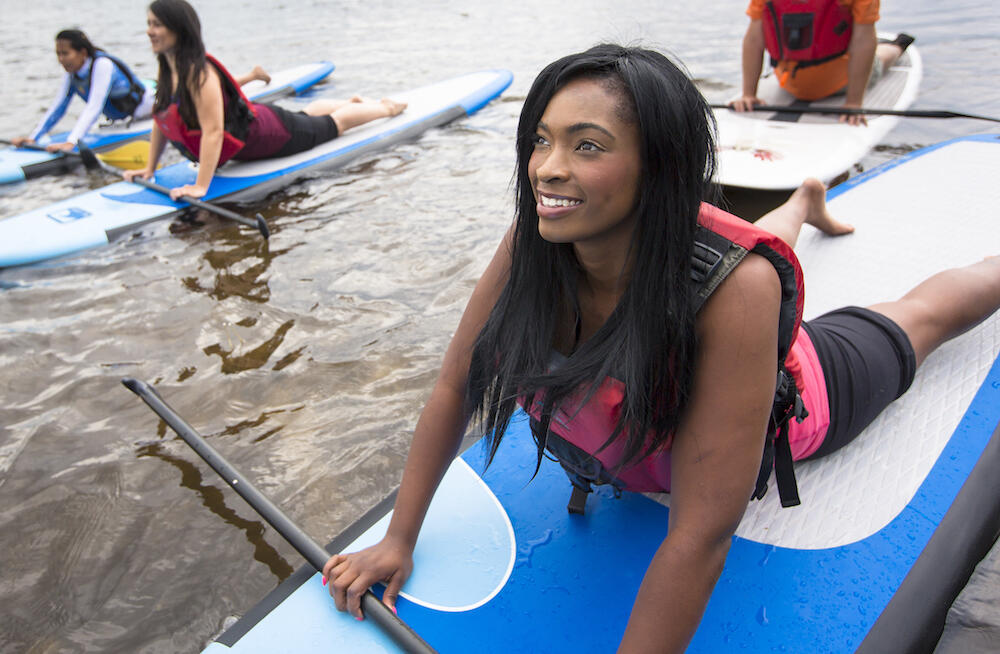 Young woman doing yoga on SUP boards