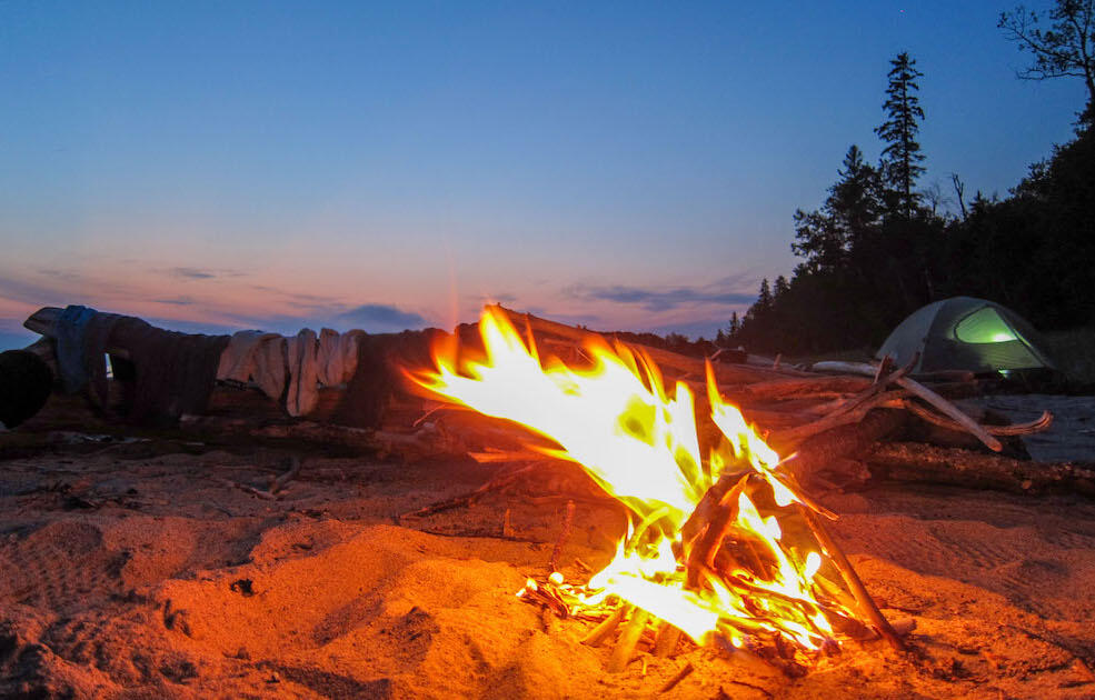 Campfire on sandy beach with tent in background