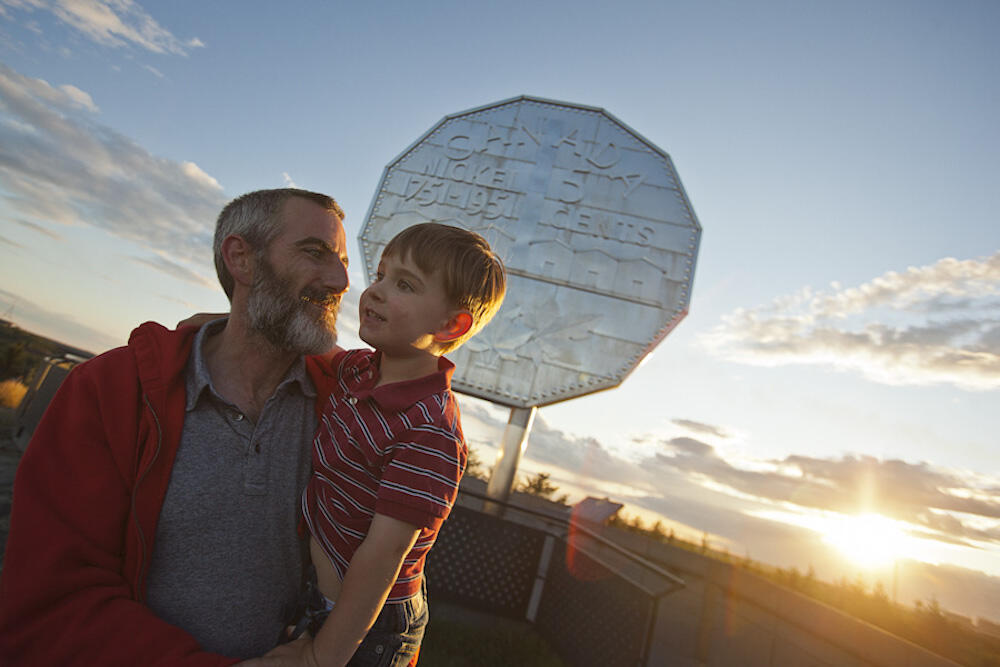 Man holding a young boy in front of the Big Nickel.