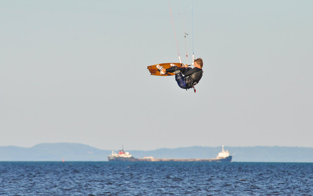 Man flying over water on a kiteboard. Ship in background