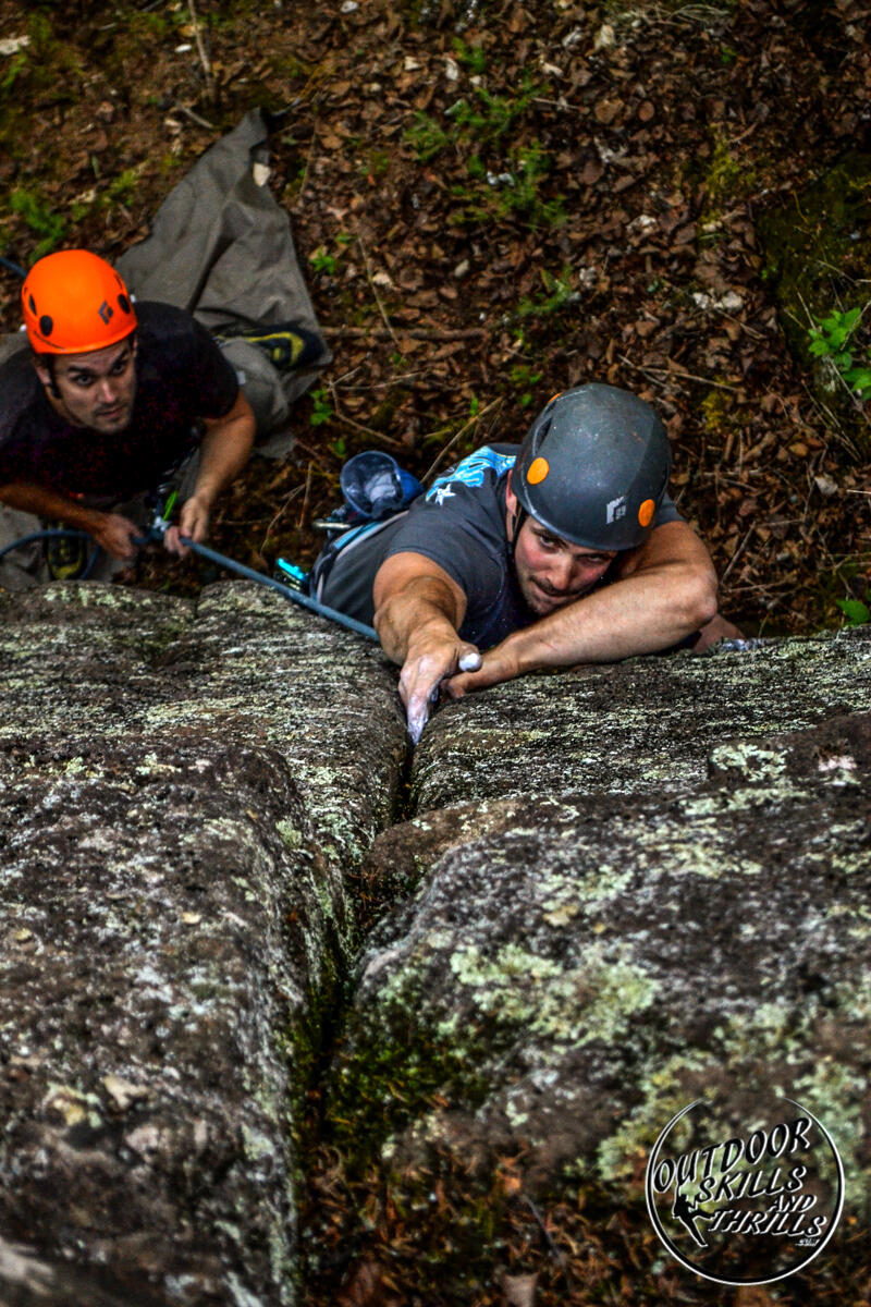 Man reaching for a hold in a crack on vertical rock face.