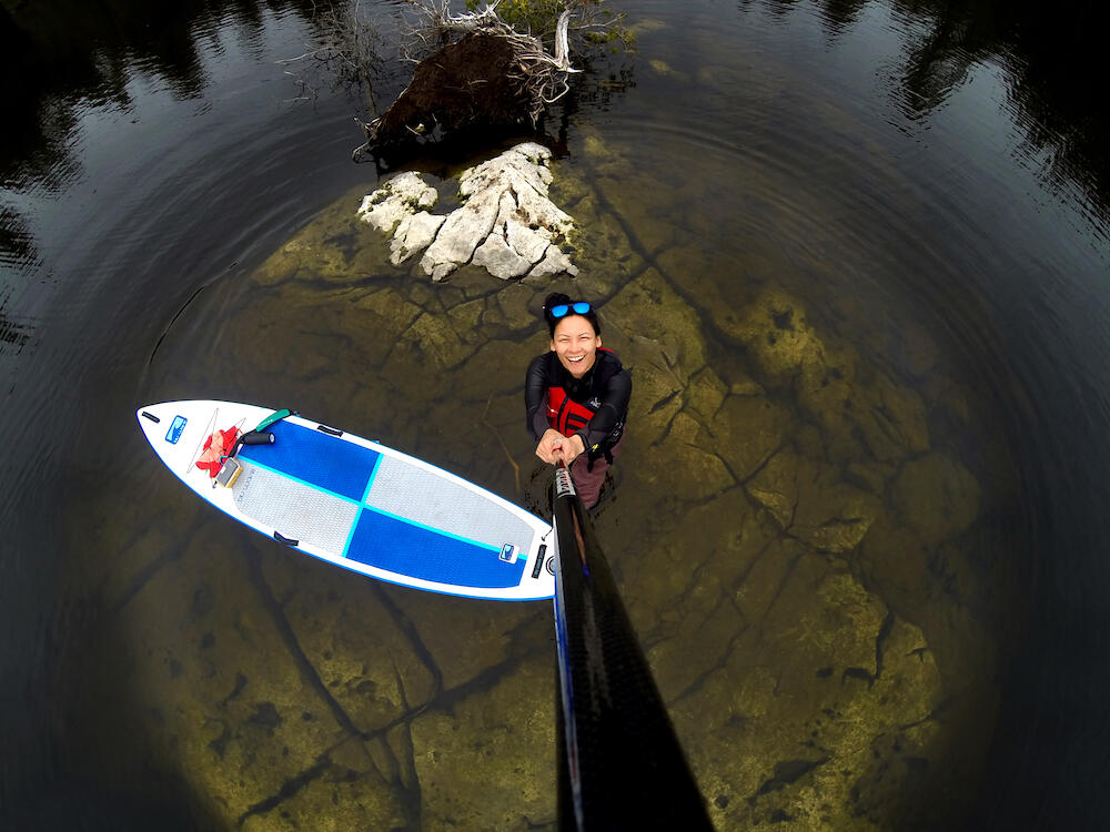 Young woman taking a selfie with paddle looking down at SUP, rocks and water.