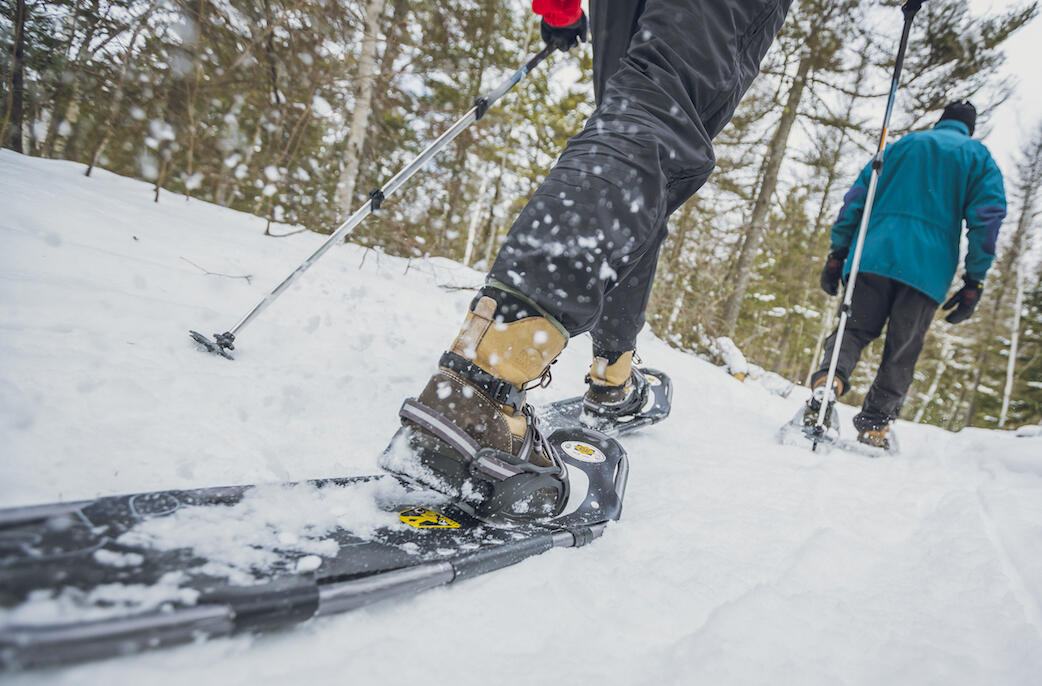 Close of of man wearing a modern snowshoe on forest trail