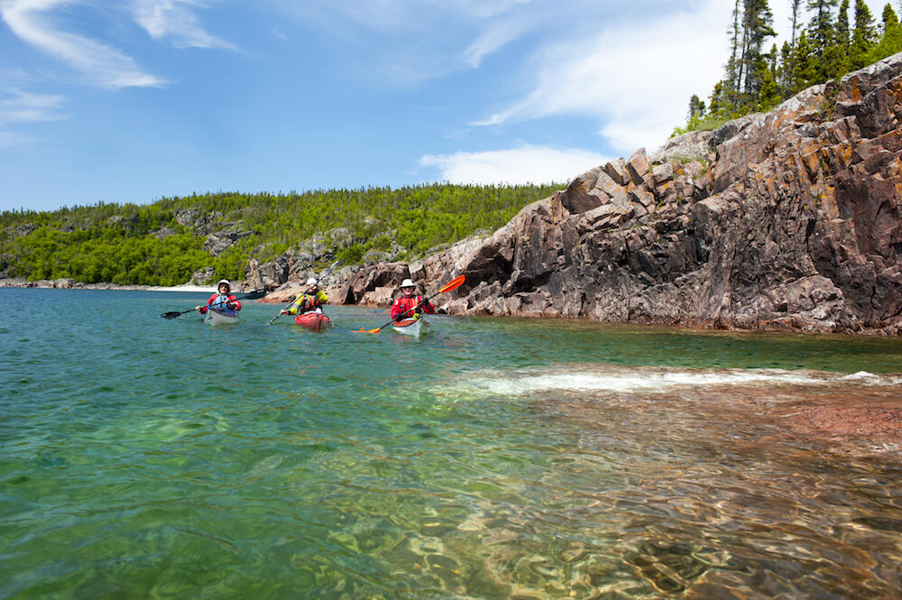 Three kayakers paddling in turquoise waters along a remote rocky shoreline