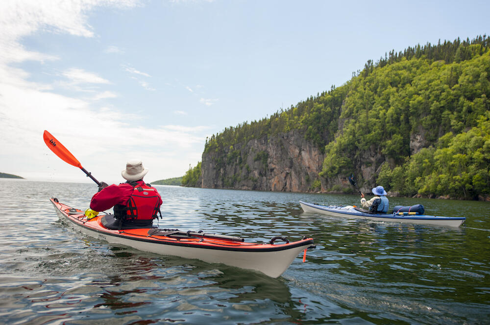 Two kayakers paddling by large cliffs on Lake Superior