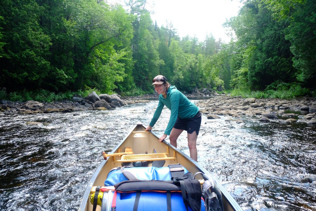 A woman standing in shallow rapids at bow of packed canoe.