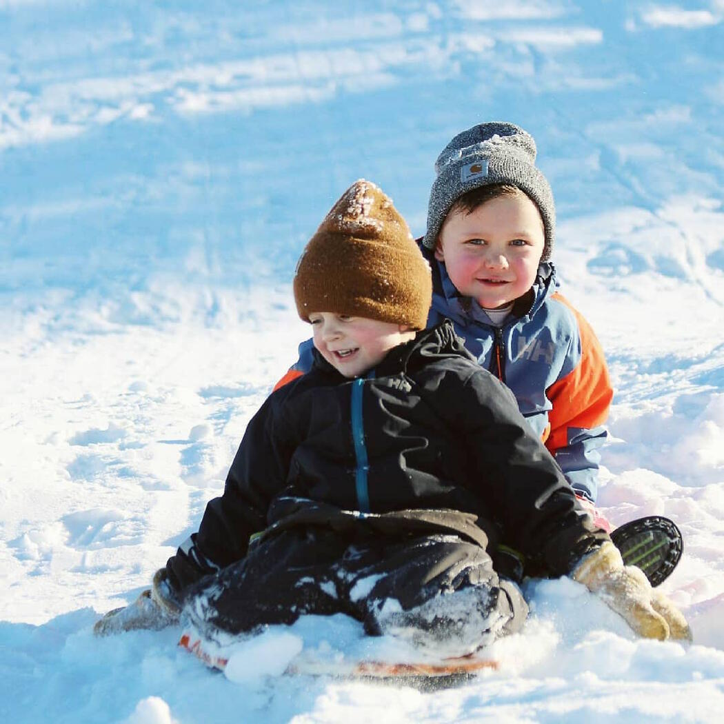 Two young boys on a toboggan.