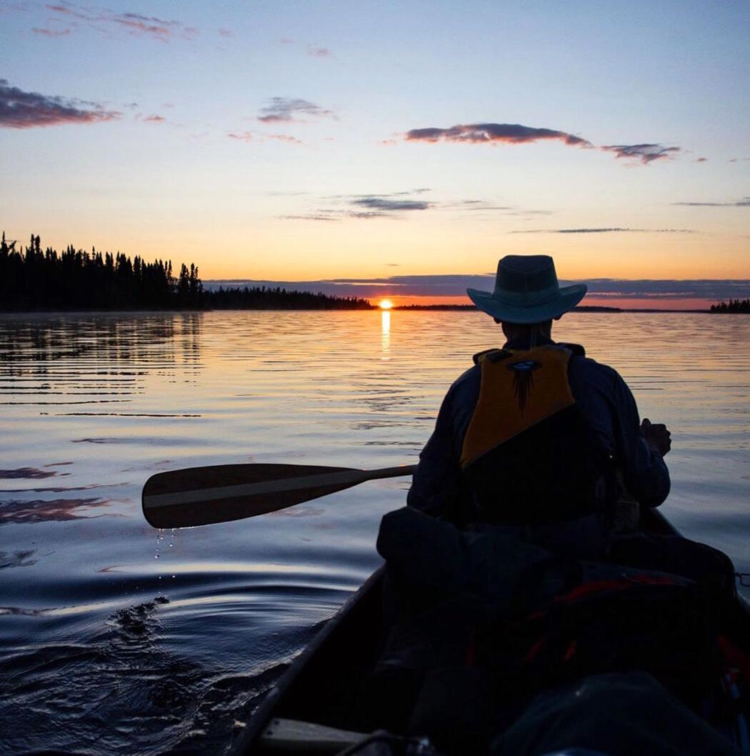Man paddling in bow of canoe at sunset.