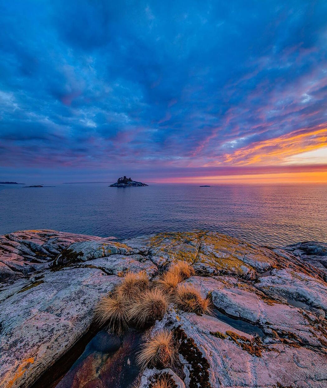 Colourful sunset over Lake Superior with smooth rocks in foreground.