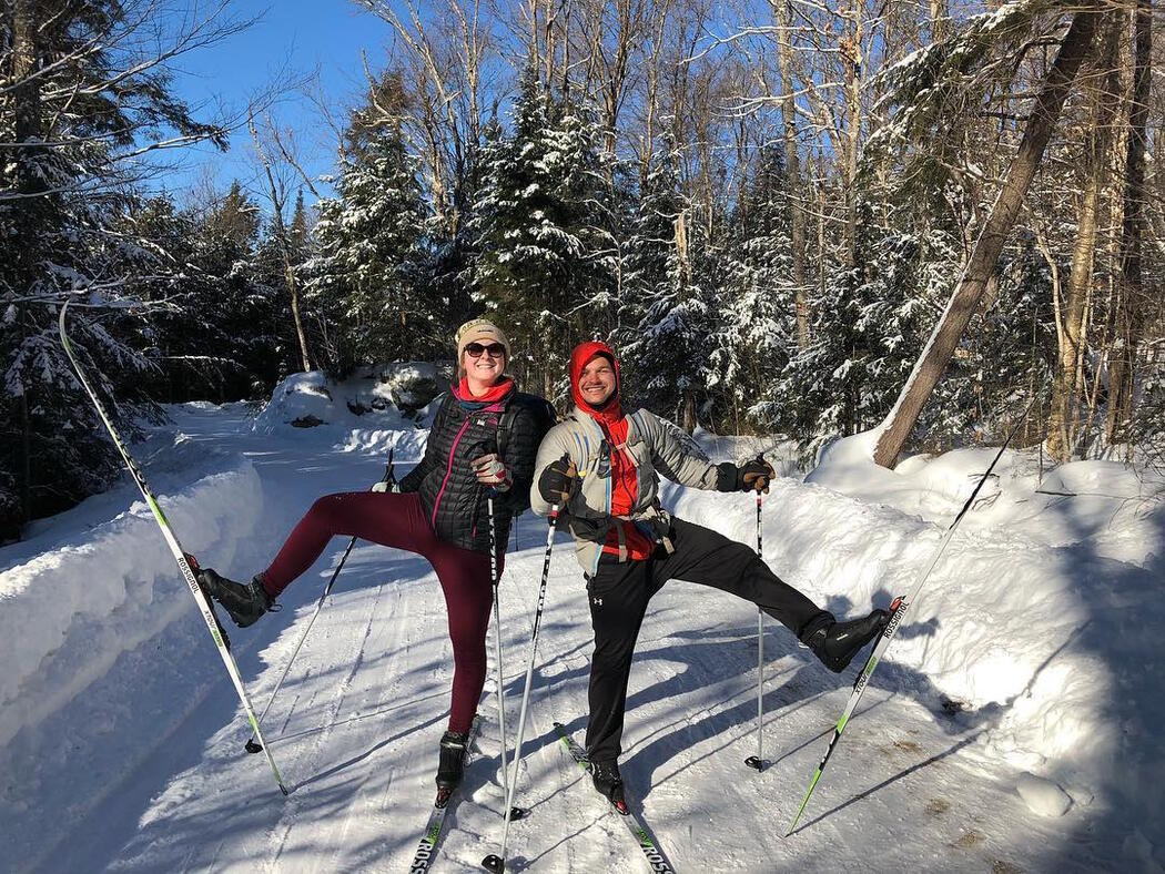 Two cross-country skiers holding up one ski.