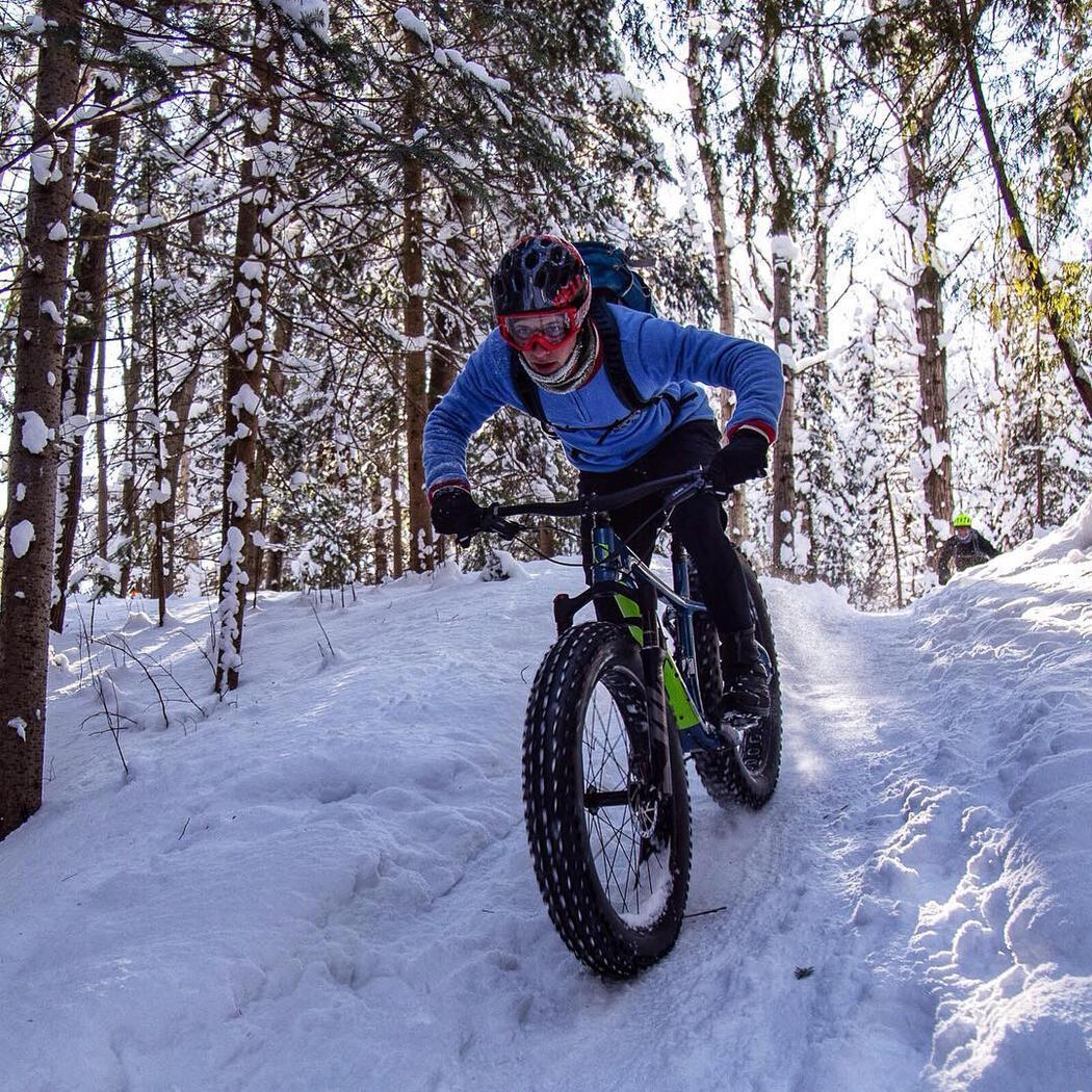 Person on a fat bike going down a small snow covered hill.