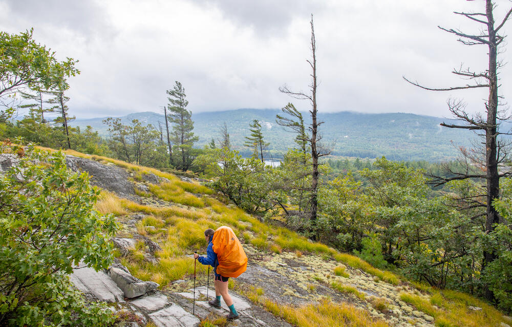 Woman with backpack hiking on a rocky trail