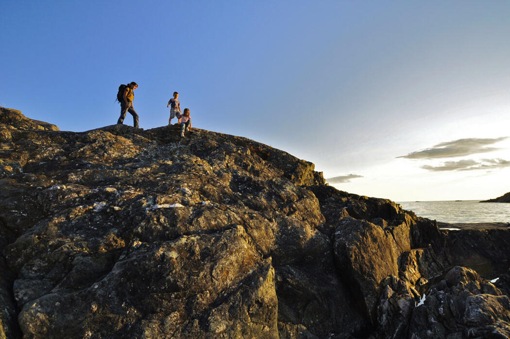Woman and two children hiking on top of rocky cliff