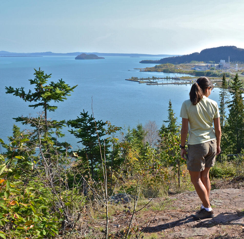 Woman standing on cliff top looking at view of Lake Superior.
