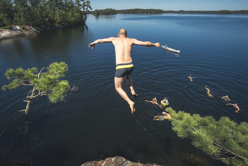 Man jumping off rock cliff into lake with several other swimmers