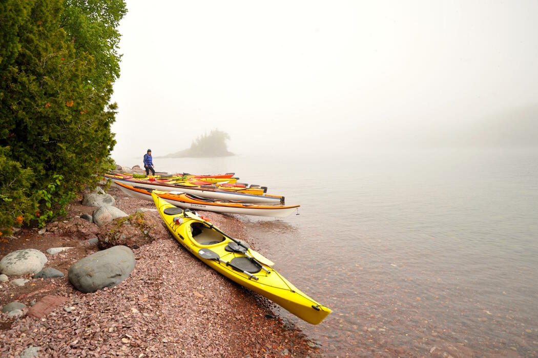 Group of empty kayaks on shore of Lake Superior, covered in by fog.