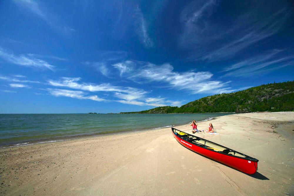 Woman and young girl sitting on an empty sand beach with red canoe in foreground