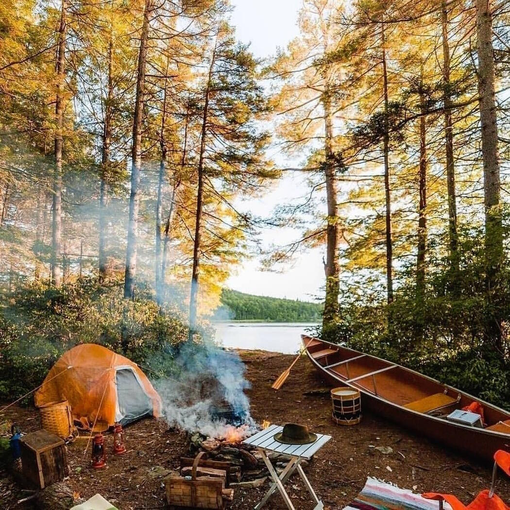 Well organized campsite with a tent, campfire, table, chairs and canoe.