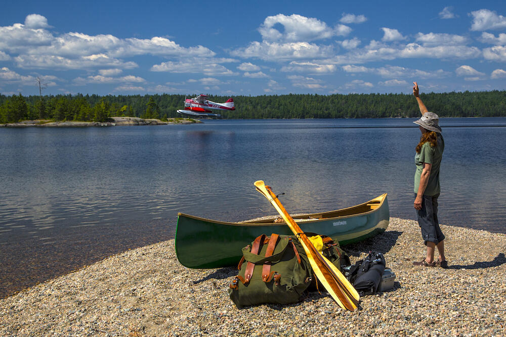 Woman on beach with a canoe and gear looking at a floatplane taking off in the distance
