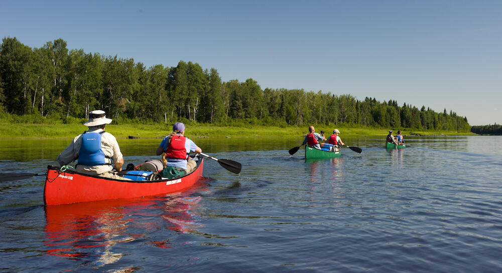 Group of canoe paddling on a wide northern river