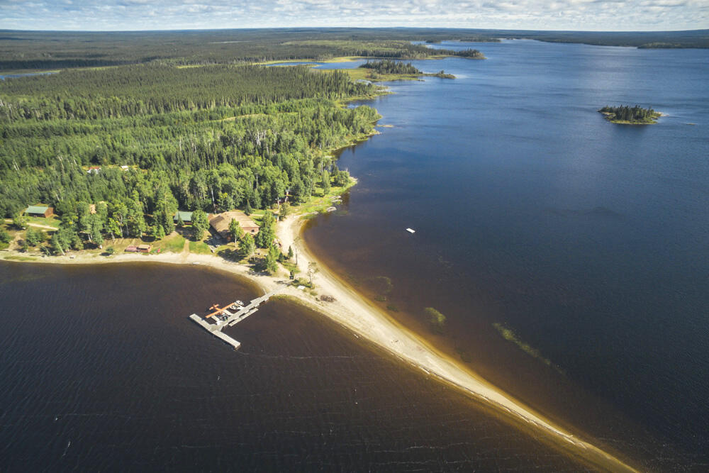 Aerial image of long sandy spit of land with large dock on beautiful lake