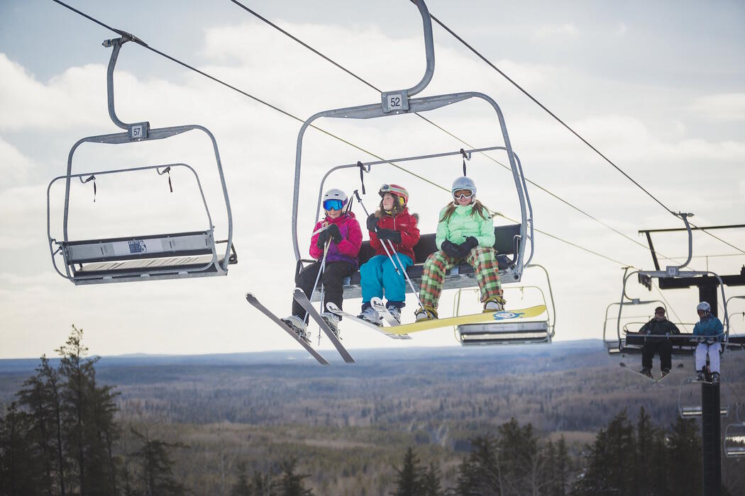 People with skiis on riding in a chair-lift.