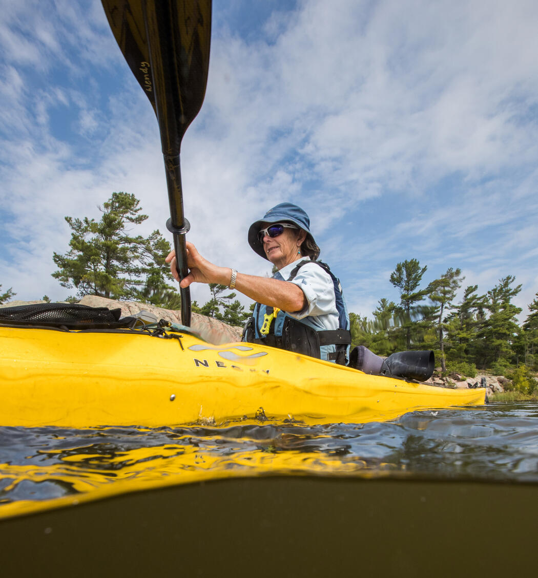 Looking up from the water at a woman in a kayak with a paddle