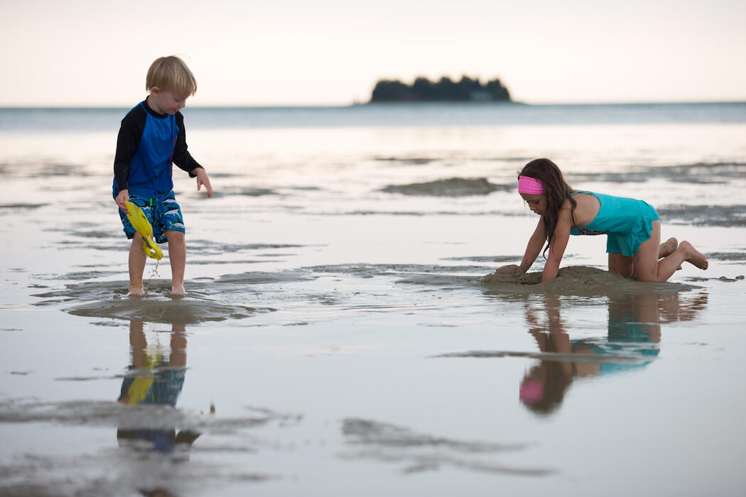 A young boy and girls playing in the shallow water on a beach.