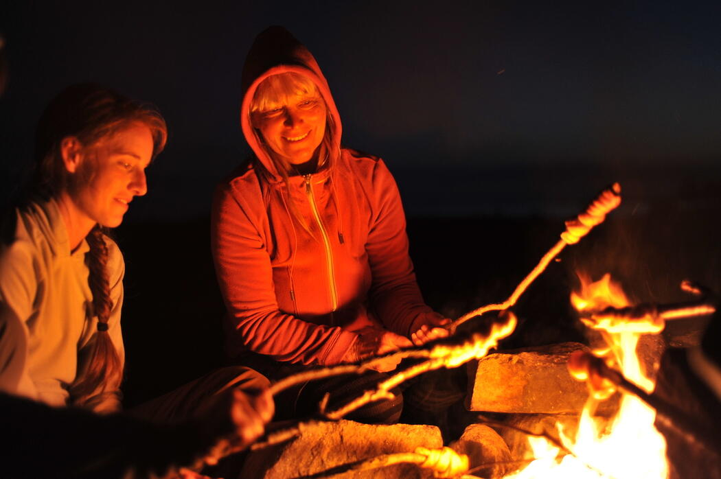 two people cooking bannock over a campfire