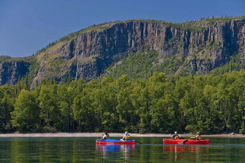 Two canoes paddling on calm water infront of large rock cliff.