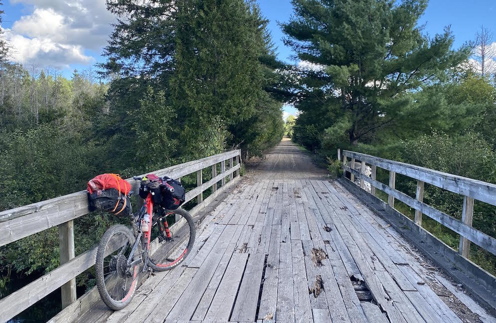 Bicycle parked on wooden bridge on a rail trail