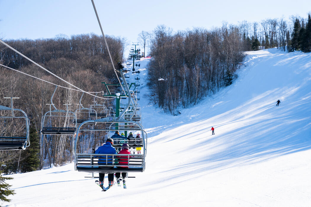 People riding a chair lift up the mountain.