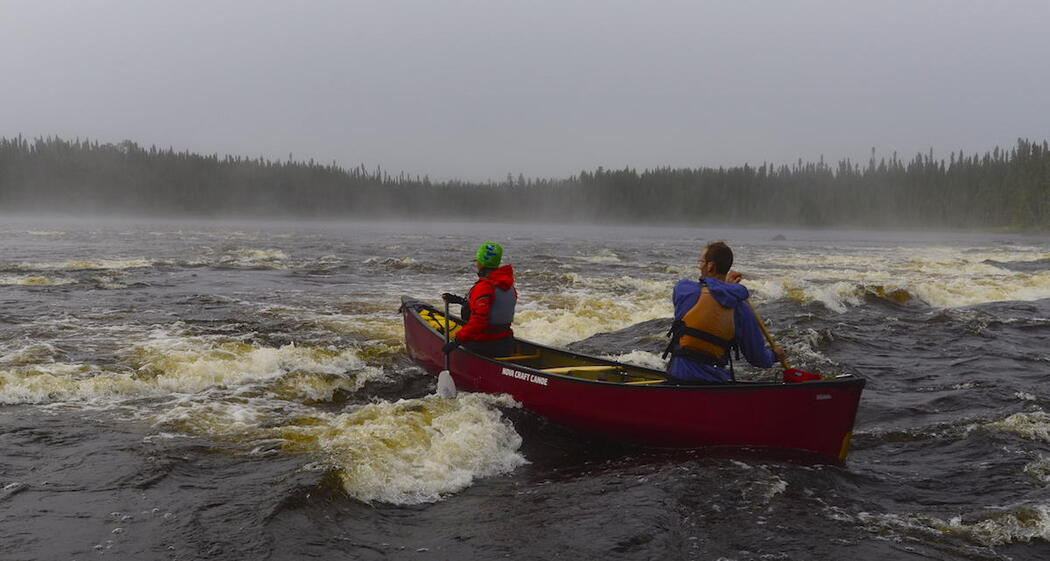 Two canoeists in red canoe paddling in whitewater.
