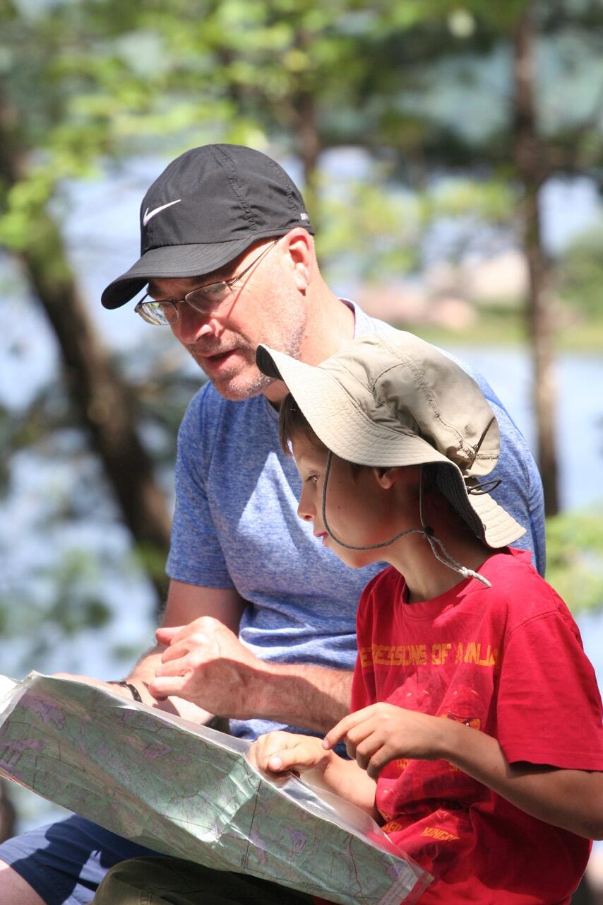 Father and son lookiing at a topo map