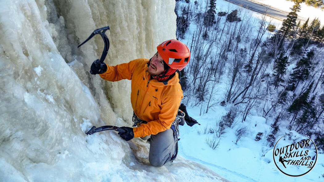 Man with ice picks climbing a frozen waterfall.