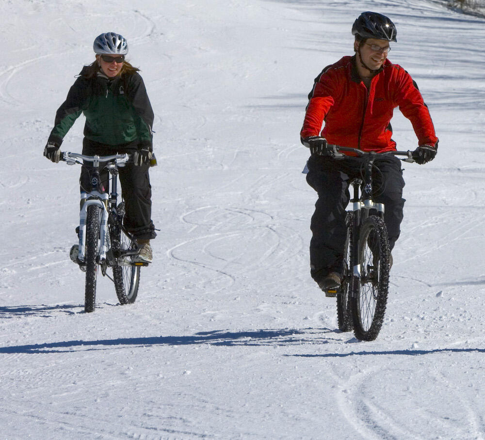 Two people riding fat bikes on snow.