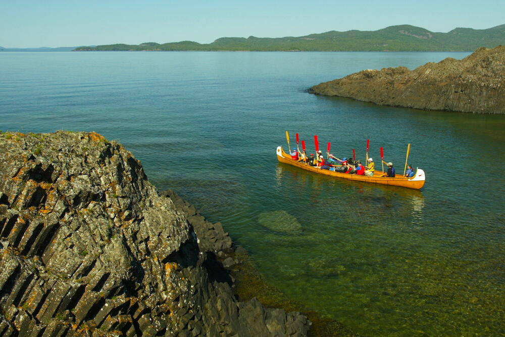 Voyageur canoe, with paddles up, in small bay on Lake Superior.