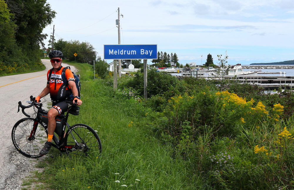 Man on a bicycle in front of Meldrum Bay road sign and marina