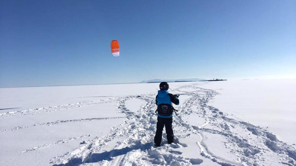 Child standing on frozen lake holding a kite.