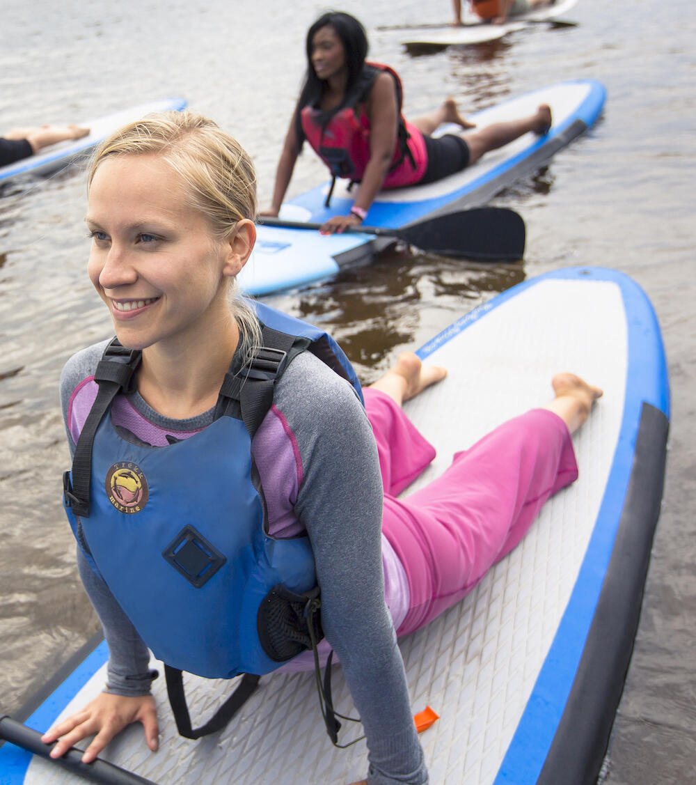 Young women doing yoga on SUP paddleboards